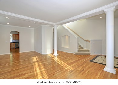 Sun filled open floorplan home interior featuring empty spacious hallway with white columns, staircase and light hardwood floor.