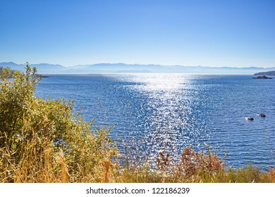 The sun filled view from Sooke Basin, Vancouver Island of  the Misty  Olympic Mountain Range, in Washington State, across Strait of Juan de Fuca, in the Pacific Ocean,
