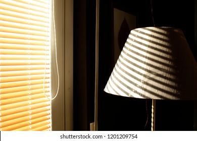 Sun filtering through shutters on grey silk lampshade