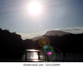 Sun flairs and water reflection on a bridge