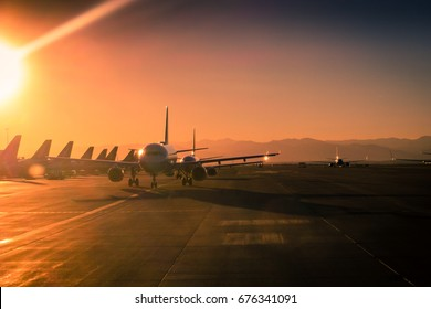 Sun Flare at the airport During Sunset with many Aircraft lined up on the Ramp and Taxi