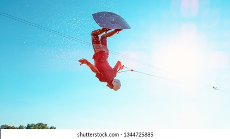SUN FLARE: Cinematic shot of an athletic young man on holiday flipping over the sun while wakeboarding in the fun cable park on the tranquil lake. Extreme athlete having fun wakeboarding in summer.