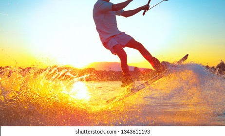 SUN FLARE, CLOSE UP: Cool surfer dude does 180 ollie while wakeboarding on a sunny summer evening. Cinematic shot of a cheerful man wakeboarding in the cool cable wake park. Awesome summer water sport