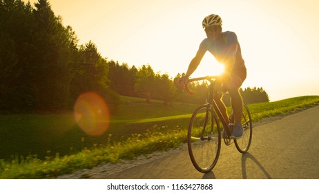 SUN FLARE: Golden evening sun rays illuminate young athletic man pedaling his cool road bicycle during a race. Caucasian cyclist enjoying picturesque ride on his bike through the sunny countryside.