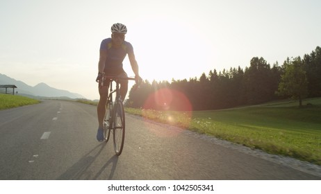 SUN FLARE: Young athlete rides his bicycle through picturesque summer nature at sunset. Beautiful golden sun rays illuminate athletic man having fun pedaling his bicycle along asphalt road