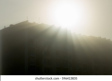 The sun in the fog from behind the house in the early morning.