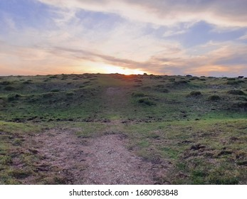 The sun gently drifts below the horizon on the South Downs, giving the once-blue sky an almost purple hue and the hillside an emerald appearance. Clouds seem to rush away from the sun.