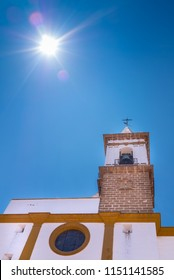 Sun glare beams against a blue sky summer day above the 16th century church Parroquia de Las Angustias  in Ayamonte, Huelva province, Andalusia, Spain.