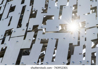 Sun glaring through metal sheets riveted together