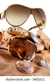 Sun glass on sand background with seashell