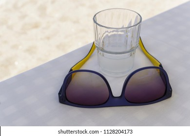 Sun glasses on restaurant table with alcoholic drink. Glass of ouzo on the rocks at Greek tavern with white linen tablecloth.