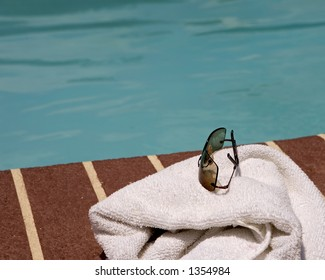 Sun glasses and towel beside a pool