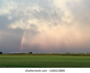 Sun glowing in the mist producing a big bright rainbow over an open farm field, left side of image