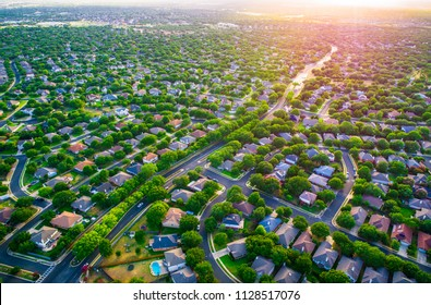 Sun glows Sunset real estate suburb homes. Community suburbia neighborhood in north Austin in suburb Round Rock , Texas Aerial drone view above new development