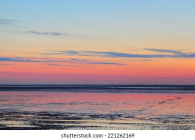 sun going down over mudflat at the german north sea coast