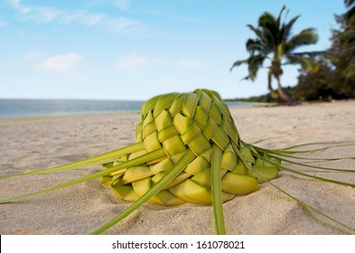 Sun hat knees out of palm leaves on sandy sea shore of tropical island.