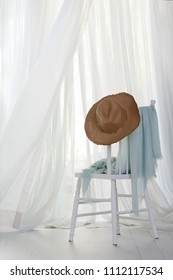 Sun hat on a white chair with a blue sarong next to an open window and a summer breeze