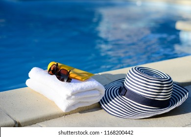 sun hat, towel, sunscreen by the poolside, swimming pool luxury summer holiday concept hotel club spa resort