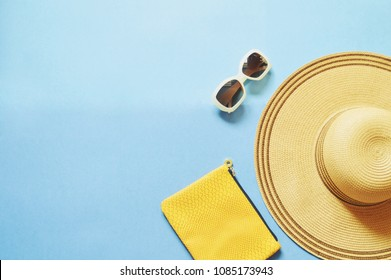 Sun hat, yellow clutch, brown sunglasses on a blue background. Flat lay beach photo. Summer travel concept, free space for text