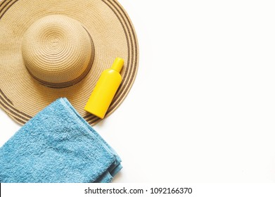 Sun hat, yellow sunscreen bottle, blue cotton towel on a white background. Feminine photography. Summer mockup. Flat lay beach accessories. Travel concept