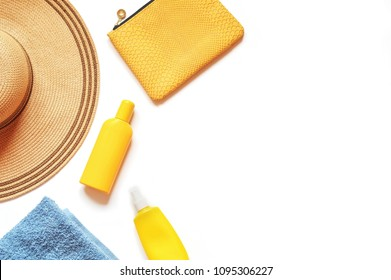 Sun hat, yellow sunscreen bottle and sunblock lotion, cosmetic bag on a white background. Mockup, free space for text. Beach holiday, summer travel photo