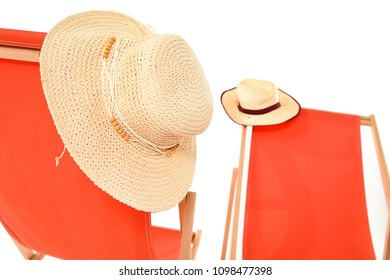 Sun hats hanging on bright orange deckchairs. With space for text.
