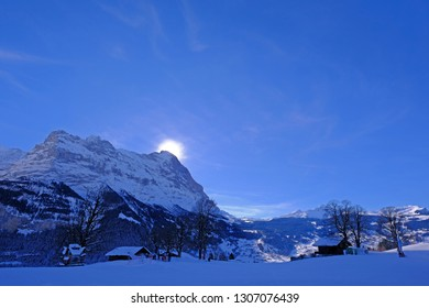 The sun hides behind the famous peak of the Eiger mountain above Grindelwald, with a lot of snow in winter season, Bern, Switzerland, Europe