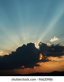 Sun hiding behind a cloud at sunset