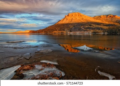 The sun illuminates the Butte at the Flatiron reservoir in Loveland Colorado. The reservoir thawing out from the winter weather