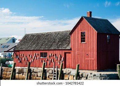 Sun illuminates famous red fishing shack, often painted by artists, referred to as Motif #1, in Rockport, Massachusetts.