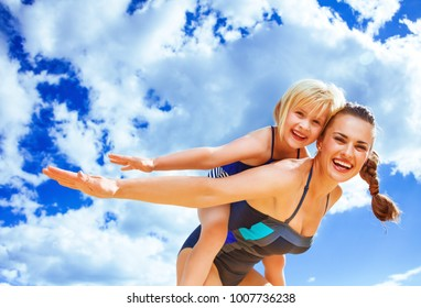 Sun kissed beauty. cheerful young mother and daughter in beachwear on the beach having fun time