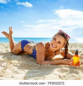 Sun kissed beauty. happy active woman in swimsuit on the seashore with sun cream