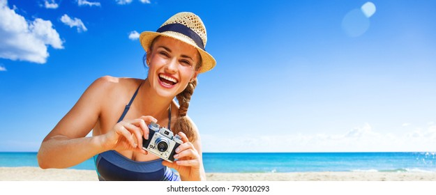 Sun kissed beauty. happy active woman in swimsuit on the seacoast with digital camera taking photo