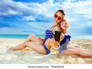 Sun kissed beauty. happy healthy mother and child in swimwear on the seashore with digital camera taking selfie