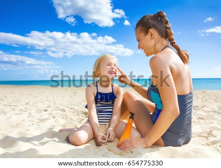 Sun kissed beauty. smiling healthy mother and daughter in beachwear on the seacoast applying sun cream