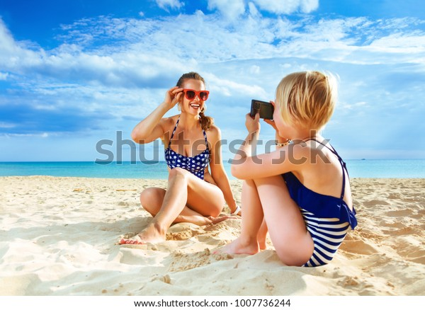 Sun kissed beauty. smiling healthy mother and daughter in swimwear on the seashore with digital camera taking photo