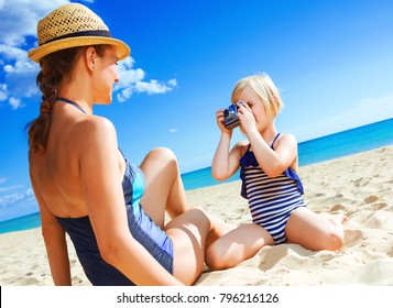Sun kissed beauty. young mother and daughter in beachwear on the seashore with retro camera taking photo