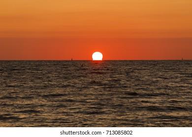 Sun kissing water in sunset over Atlantic ocean
