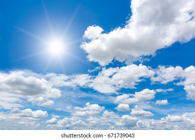 Sun with lens flare in blue sky above clouds.