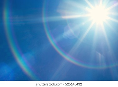 Sun with lens flare, on blue sky background.