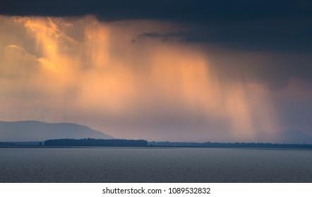 sun light beam prenetrate the cloud over the lake