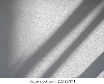 The sun light casting abstract shadow over the white concrete wall,sunshade shadow