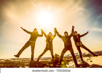 sun light fall on the friends. Friends holding hands and have fun on flank of hill. team of young people outdoor winter setting. Jumping in joy! hands up. sunny winter day.