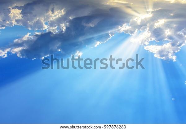Rayons ou poutres de lumière du soleil éclatant des nuages sur un ciel bleu. Arrière-plan religieux spirituel.