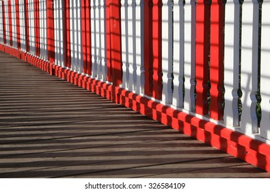 Sun light and shadow on white-red wooden balustrade.