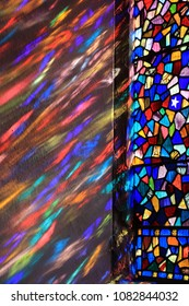 Sun light streaming through a stained glass window in Sussex, UK