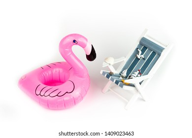 Sun lounger and inflatable Flamingo isolated on white background. Tropical vacation background. Sun lounger on the sandy island, copy space, front view