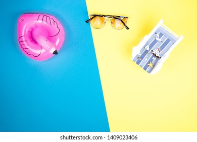 Sun lounger, inflatable Flamingo and sunglasses isolated on colourful background. Tropical vacation background. Sun lounger on the sandy island, copy space, top view