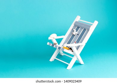 Sun lounger isolated on blue background. Tropical vacation background. Sun lounger on the sandy island, copy space, front view