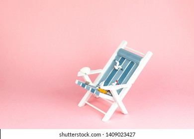 Sun lounger isolated on pink background. Tropical vacation background. Sun lounger on the sandy island, copy space, front view